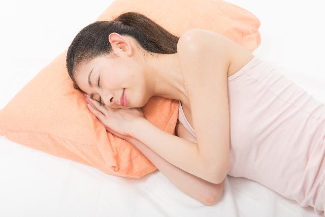 まくらで寝る女性